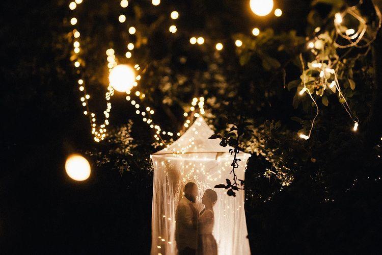 Zamilovaný pár pod baldachýnom na záhrade Zeleného dňa počas svadobného večera