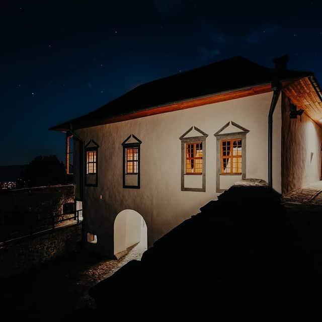 Lubovniansky hrad počas večera s vysvietenými oknami a celkovou tajomnou, no podmanivou atmosférou