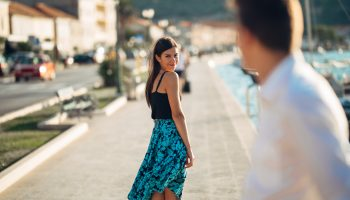 Young,Attractive,Woman,Flirting,With,A,Man,On,The,Street.flirty