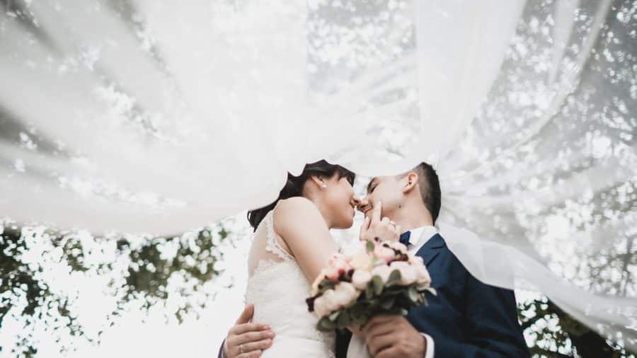 svadobný pár bozkávajúc sa pri svadobnom obrade pod závojom nevesty