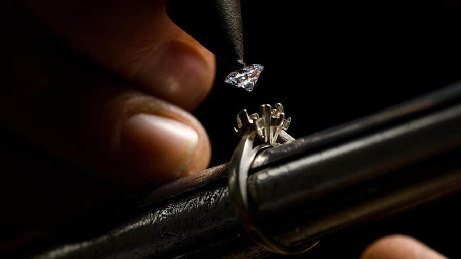 Zlatník osádza diamant do zásnubného prsteňa